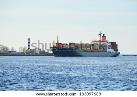 Large cargo container ship sailing. Riga, Latvia