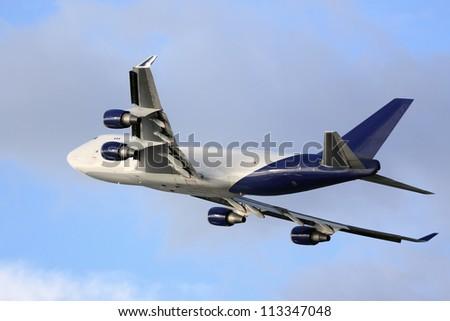 Large cargo jumbo jet climbing into blue sky - stock photo