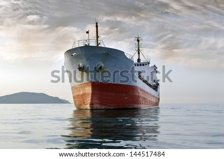 large cargo ship at sea  background of grey sky in the calm - stock photo