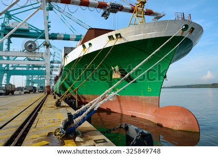 Large cargo ship being loaded in a port Johor, Malaysia. - stock photo