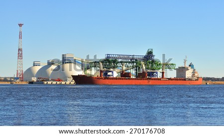 Large cargo ship (Bulk carrier) sailing in a bright sunny day.