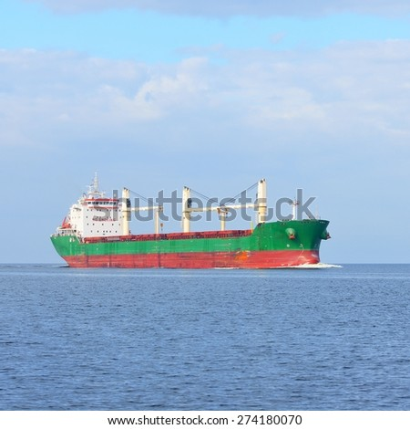 Large cargo ship (Bulk carrier) sailing in a bright sunny day