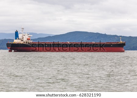 Large cargo ship in an ocean bay with mountains.