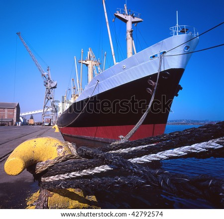 large cargo ship offloading in harbor - stock photo