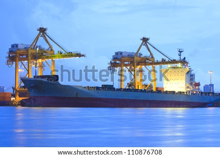 Large cargo ship on loading in the port at night. - stock photo
