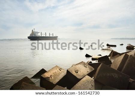 Large cargo ship sailing entering port of Riga - stock photo