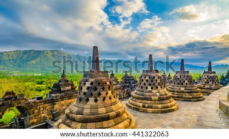 Large carved stone bells at the apex of the worlds largest ninth century Buddhist temple. The temple is also listed as a world heritage site. In the background is mountains covered lush green foliage.