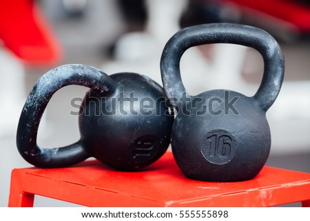 Large cast-iron sixteen pound weight dumbbell on gym background.