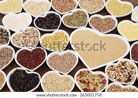 Large cereal and grain food selection in heart shaped porcelain bowls over lokta paper background. Amaranth in the largest dish. - stock photo