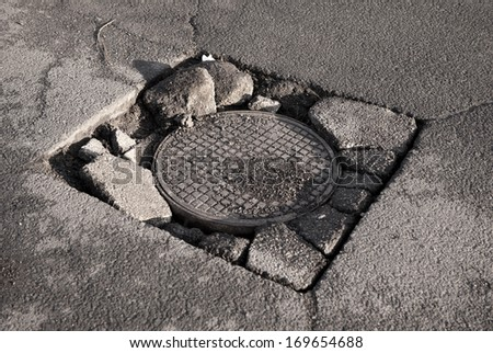 Large chuckhole in asphalt and circular manhole cover of sewage well in road, close metal sewer cover in Warsaw, Poland, horizontal orientation, nobody. - stock photo