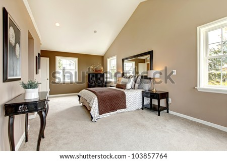 Large classic luxury bedroom with brown and white and beige carpet. - stock photo