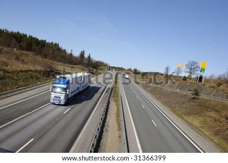large clean truck on highway surrounded by country-side - stock photo