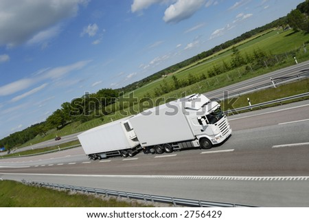 large clean-white truck speeding on highway with countryside panorama in background - stock photo