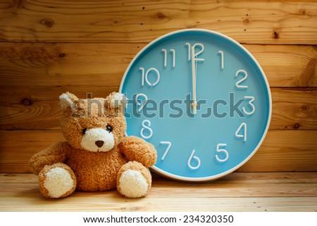 large clock blue face on wood background. - stock photo