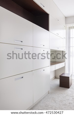 Large closet with white cabinets in a very bright interior