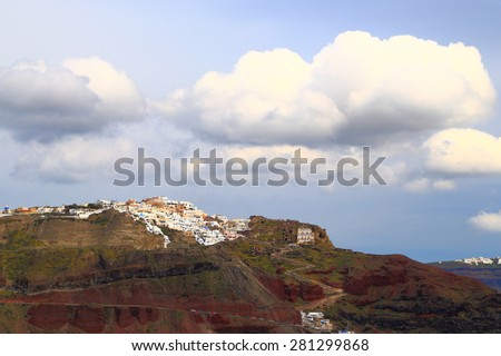 Large clouds above distant houses of Oia village built on volcanic rock, Santorini island, Greece - stock photo