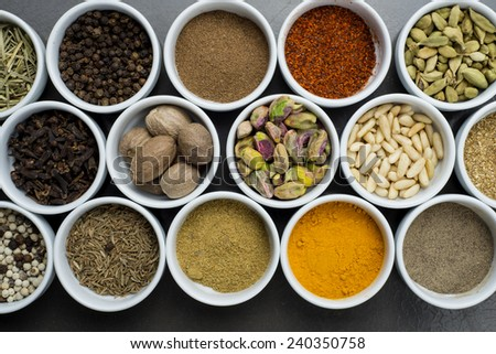 large collection of different spices and herbs isolated on dark background  - stock photo