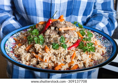 Large color Uzbek pilaf dish with spicy red pepper and fresh cilantro holds girl in checkered shirt