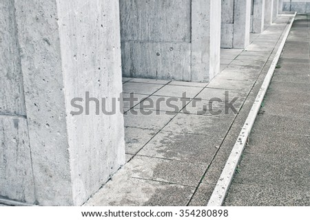 Large concrete pillars at the base of an urban building