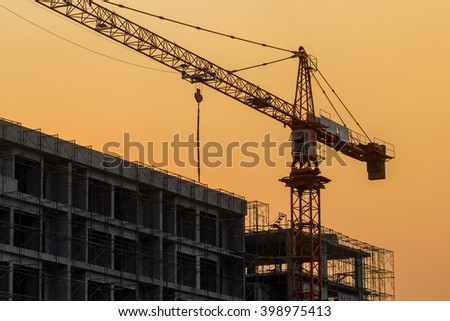 large construction with a big crane on the sunset