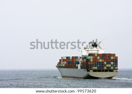 Large container cargo ship heading out to sea.