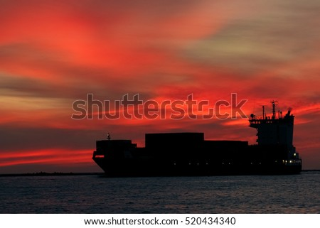 Large container ship silhouette arriving from Baltic sea at red sunset sky