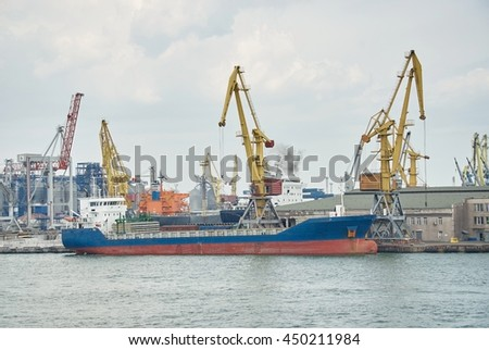Large container vessel in Port of Odessa. Cargo cranes on rails and cargo warehouses in the seaport.