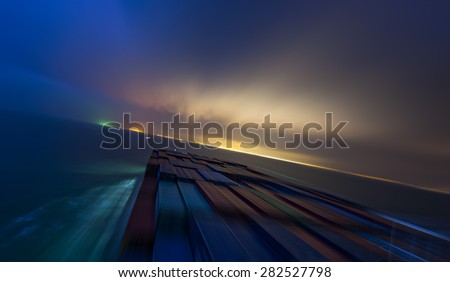 Large container vessel ship approaching coast line by night. Motion Blur
