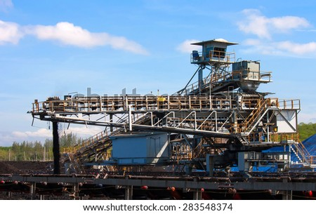 Large conveyor belt carrying coal and emptying onto a huge pile. - stock photo