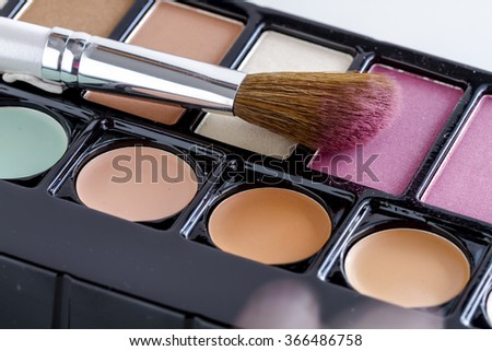 Large cosmetic brush with pink blush dust sitting on palette of blush and skin cover up colors - stock photo