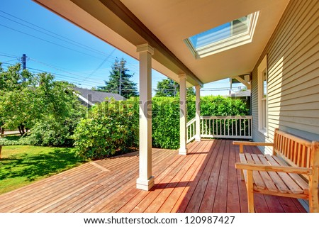 Large covered porch with skylight and wood bench and floor with summer landscape.