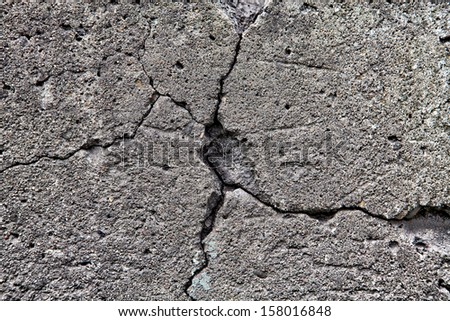 Large cracked stone wall background texture - stock photo