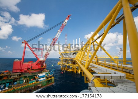 Large crane vessel installing the platform in offshore,crane barge doing marine heavy lift installation works in the gulf or the sea - stock photo