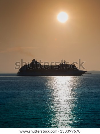 Large cruise ship at sunset off to sea. - stock photo