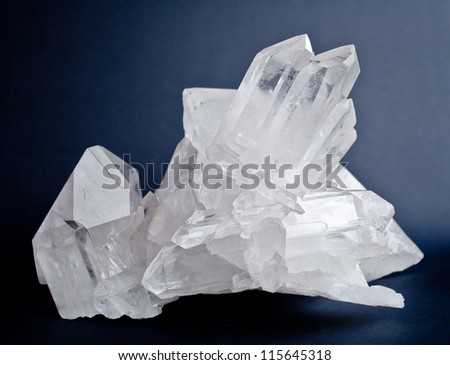 Large crystals of white quartz on dark blue background - stock photo