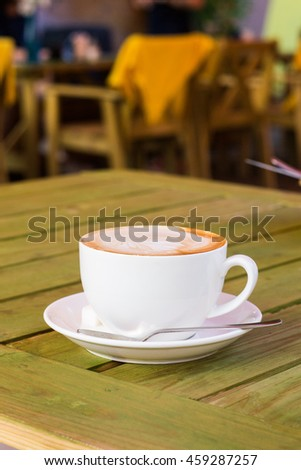 Large cup of coffee on a wooden table in a street cafe, closeup
