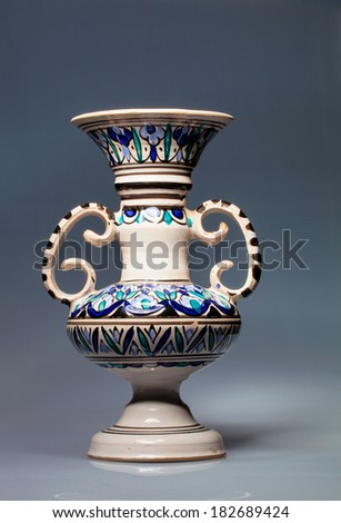 large decorative vase with two ears,on a blue background - stock photo