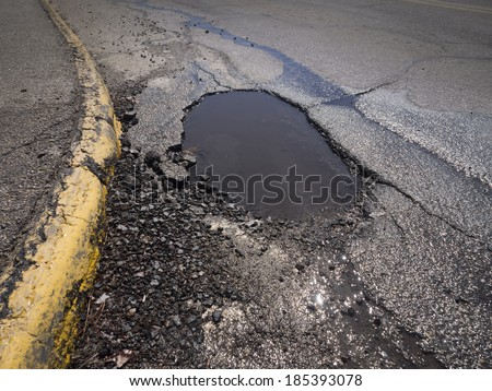 Large deep pothole as an example of poor road maintenance due to cutbacks on the infrastructure budget - stock photo