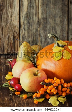Large delicious pumpkin and different fresh fruit on wooden background. Bio healthy food. Organic vegetables.  Rustic style. Selective focus. Toned image