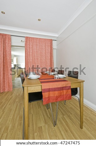 large dining table with red table cloth and setup