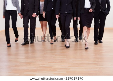 Large diverse group of business executives approaching walking towards the camera led by a woman - stock photo