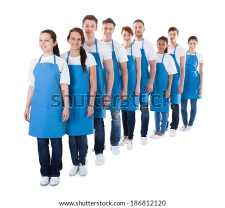 Large diverse group of cleaners or janitors standing in a queue in a receding diagonal line to the camera wearing blue aprons  isolated on white