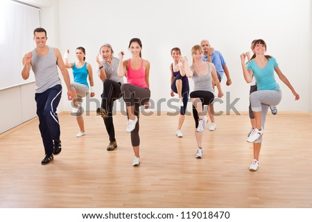 Large diverse group of people doing aerobics exercises in a class in a gym in a health and fitness concept - stock photo