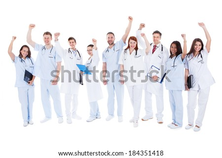Large diverse multiethnic medical team standing cheering and punching the air with their fists as they celebrate a success or motivate themselves  isolated on white - stock photo
