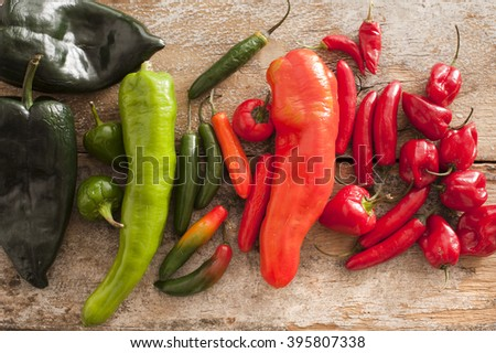 Large diverse selection of colorful poblano serrano and habanero peppers on a rustic wooden table - stock photo