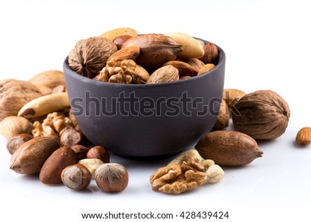 Large diversity of healthy nuts in a dark stone bowl - isolated