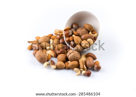 Large diversity of healthy nuts in a white bowl - isolated - stock photo