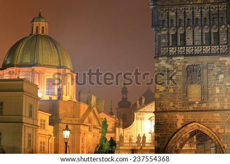Large dome and Gothic tower near the Charles bridge in foggy night, Prague, Czech Republic - stock photo