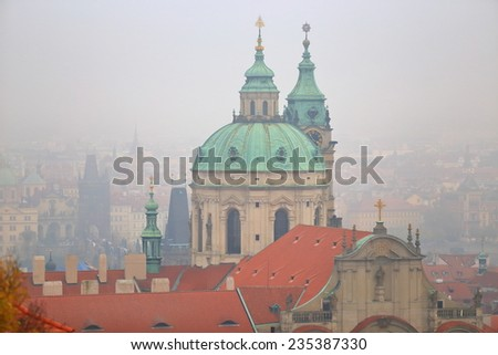 Large dome of Saint Nicholas Church (Cathedral) above orange roof tops in foggy day, Prague, Czech Republic - stock photo