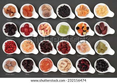 Large dried fruit selection in white bowls over slate background with titles. - stock photo